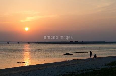 オレンジ色の夕日と飛行場の誘導灯とシルエットの二人の写真素材 [FYI04293175]