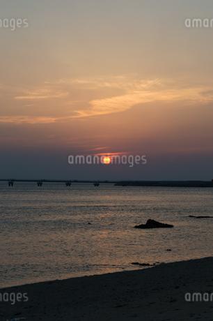 オレンジ色の夕日と飛行場の誘導灯と砂浜の写真素材 [FYI04293176]