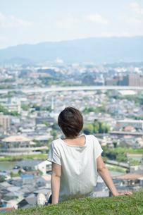 高台で市街地を見下ろす女性の後ろ姿の写真素材 [FYI04293529]