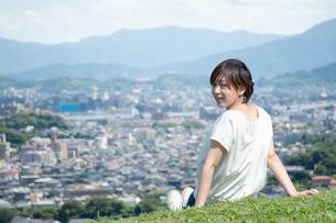 高台で市街地を見下ろしながら振り返す女性の写真素材 [FYI04293530]