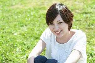 草原に座って微笑む女性の写真素材 [FYI04293544]