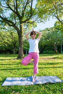 公園で微笑みながらヨガをする女性の写真素材 [FYI04293582]