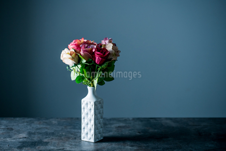 Artificial antique roses in vase on dark background.の写真素材 [FYI04293621]