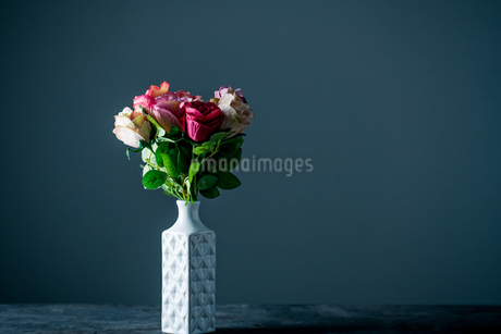 Artificial antique roses in vase on dark background.の写真素材 [FYI04293622]