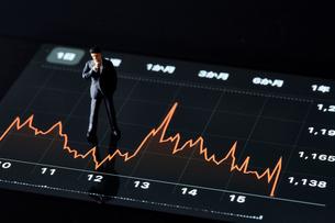 スマートフォンの画面の上でグラフを見るミニチュア人形の写真素材 [FYI04294144]