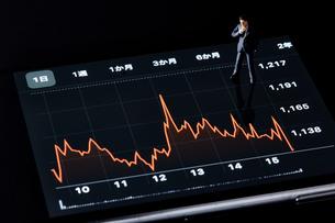 スマートフォンの画面の上でグラフを見るミニチュア人形の写真素材 [FYI04294145]