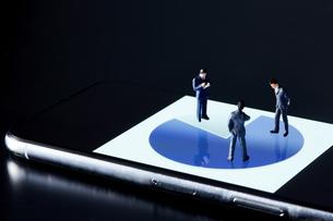スマートフォンの画面の上でグラフを見るミニチュア人形の写真素材 [FYI04294146]