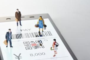 スマートフォンのキャッシュレス画面の上にいる人形の写真素材 [FYI04294150]