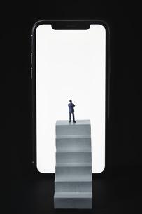スマートフォンの画面の前の小さな階段とミニチュア人形の写真素材 [FYI04294154]