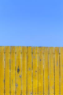 青空と黄色の古びた板塀。背景用素材の写真素材 [FYI04295007]
