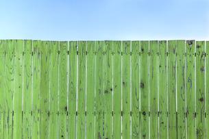 青空と緑の古びた板塀。背景用素材の写真素材 [FYI04295016]