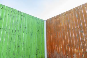 緑と茶色に塗装された古びた板塀のコーナー。背景用素材の写真素材 [FYI04295027]