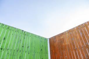 緑と茶色に塗装された古びた板塀のコーナー。背景用素材の写真素材 [FYI04295028]