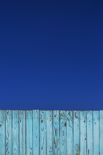 青空と青色の古びた板塀。背景用素材の写真素材 [FYI04295037]