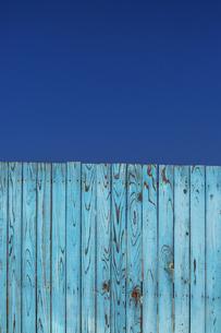 青空と青色の古びた板塀。背景用素材の写真素材 [FYI04295038]