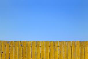 青空と黄色の古びた板塀。背景用素材の写真素材 [FYI04295044]