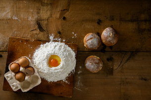Breads and flour with some eggs. Fresh breads on wooden board background.の写真素材 [FYI04295189]