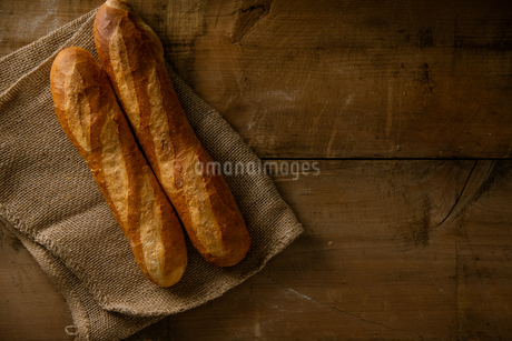 Baguettes with burlap sack on woody background.の写真素材 [FYI04295191]