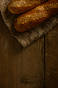 Baguettes with burlap sack on woody background.の写真素材 [FYI04295193]