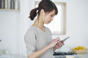 キッチンでスマートフォンを操作する女性の写真素材 [FYI04296148]