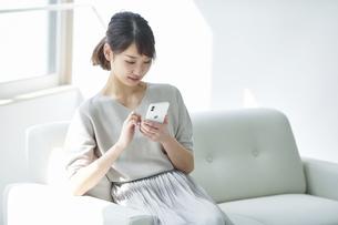 ソファに座りスマートフォンを持つ女性の写真素材 [FYI04296157]