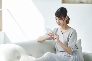 ソファに座りスマートフォンを持つ女性の写真素材 [FYI04296160]