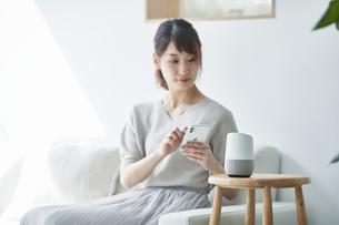 ソファに座りスマートフォンを操作する女性の写真素材 [FYI04296166]