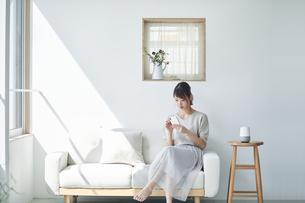ソファに座りスマートフォンを操作する女性の写真素材 [FYI04296168]