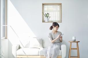 ソファに座りスマートフォンを操作する女性の写真素材 [FYI04296171]