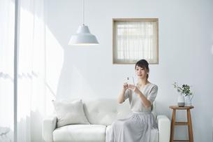 ソファに座りスマートフォンを操作する女性の写真素材 [FYI04296177]