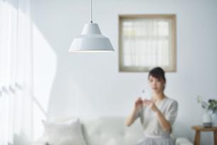 ソファに座りスマートフォンを操作する女性の写真素材 [FYI04296178]
