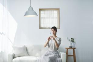 ソファに座りスマートフォンを操作する女性の写真素材 [FYI04296179]