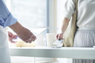 カフェでキャッシュレス決済をする女性の写真素材 [FYI04296412]