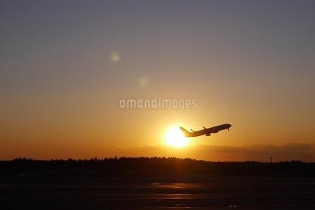 夕焼けに離陸する飛行機の写真素材 [FYI04296519]