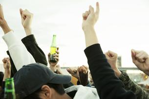 瓶ビールを持ち盛り上がる男女の写真素材 [FYI04296977]