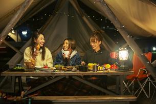 屋外ディナーをする笑顔の20代女性3人の写真素材 [FYI04297114]