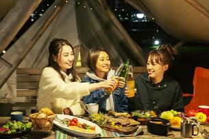 屋外ディナーをする笑顔の20代女性3人の写真素材 [FYI04297119]