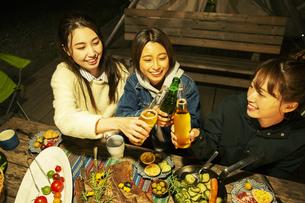 屋外ディナーをする笑顔の20代女性3人の写真素材 [FYI04297121]