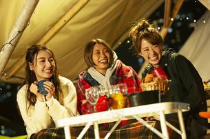屋外でのディナーを楽しむ笑顔の20代女性3人の写真素材 [FYI04297130]