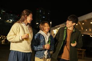 瓶ビールを持ち会話をする20代男女の写真素材 [FYI04297180]