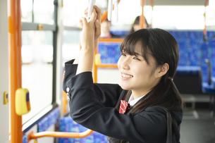 バスの中でつり革につかまる女子学生の写真素材 [FYI04298222]