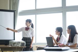 ホワイトスクリーンの前で指示棒を持つ女子学生の写真素材 [FYI04298246]