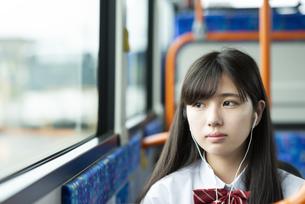 バスの中で音楽を聴く女子学生の写真素材 [FYI04298288]