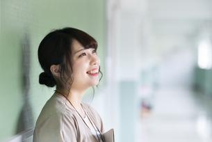 廊下で掲示物を見つめる女子学生の写真素材 [FYI04298313]