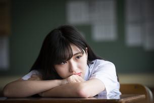 教室で考え事をする女子学生の写真素材 [FYI04298317]