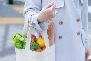 スーパーマーケットで買物した食品をエコバッグに入れて歩く女性の写真素材 [FYI04300796]