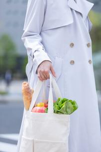 スーパーマーケットで買物した食品をエコバッグに入れて歩く女性の写真素材 [FYI04300797]