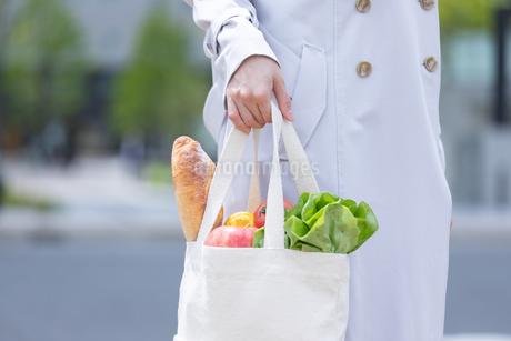 スーパーマーケットで買物した食品をエコバッグに入れて歩く女性の写真素材 [FYI04300800]