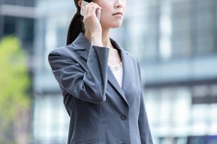 オフィス街でスマートフォンで電話をする若いビジネスウーマンの写真素材 [FYI04300802]