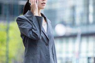 オフィス街でスマートフォンで電話をする若いビジネスウーマンの写真素材 [FYI04300803]